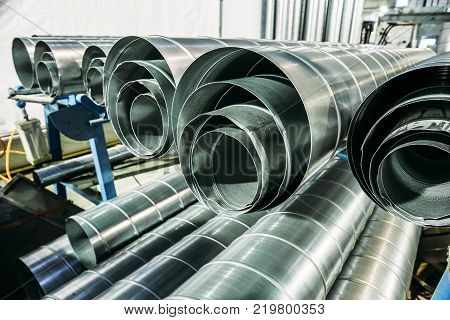 Round metal or steel or galvanized iron tubes or pipes in metalworking workshop or factory