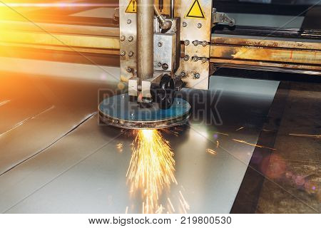 CNC programmable laser plasma cutting machine cuts sheet of metal with sparks, modern industrial metalwork technology, professional manufacturing equipment poster