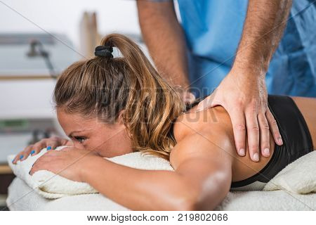 Physical therapy. Therapist applying strong pressure to shoulder muscles. Woman patient