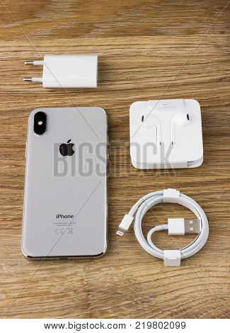 Rostov-on-Don, Russia - December 12, 2017: Iphone 10 rests on a wooden table next to the cable, charger and headset earpods.
