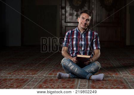 Young Muslim Guy Reading The Koran