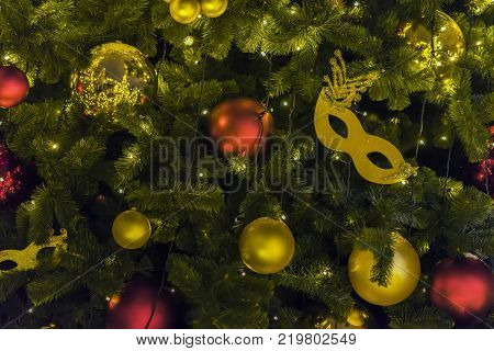 Golden carnival mask and colorful bright shiny celluloid balls on Christmas tree. Festive occasions concept, Christmas, Winter holiday, Happy New Year