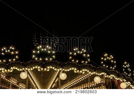 Illuminated golden bright Carousel with bright lights, silhouette on night city, romantic, nostalgic mood, melancholy, festive occasions, with copy space