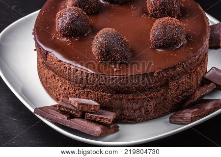 Homemade chocolate biscuit cake and dark chocolate segments on a white plate