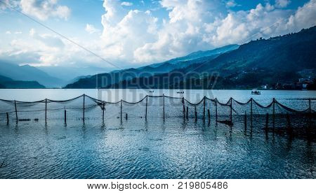 Fishing net pulled in a line on the Phewa lake, Pokhara. Beautiful view of mountains on the background.