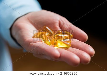White medication capsules of glucosamine healthy supplement pills in woman palm hand demonstrate one pill.