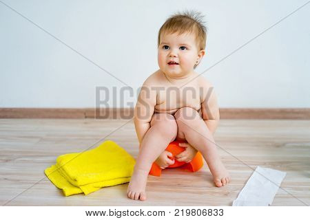 Cute smiling baby sitting on the potty