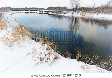 Winter landscape. The banks of the river covered with snow