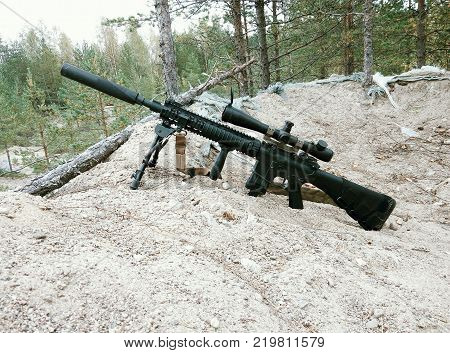 Assault rifle on the background of pine forests and sand.