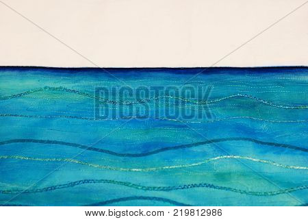Photo of a beautiful seascape painting on textile using fabric paints in blue and turquoise. Painting stitched using threads and ribbons with a zigzag stitch to create wave shapes. With space for text.