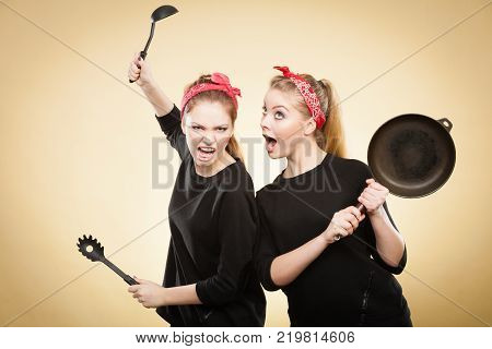Disagreement in cooking. Kitchen accessories equipment in move. Girls having argument fight. Expression of fear and anger.