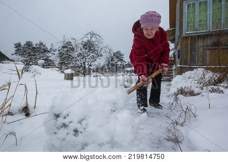 An elderly woman cleans snow near his home in the village.
