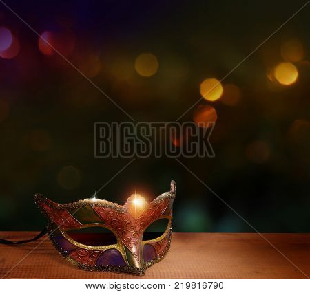 Traditional female carnival venetian mask; on table .Masquerade; mask on; glitter background.Mardi Gras.