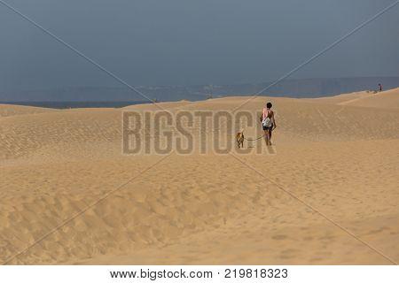 ALBUFEIRA, PRAIA DA BORDEIRA, PORTUGAL - AUGUST 20, 2017: People at the dunes of the famous beach of Praia da Bordeira. This beach is a part of famous tourist region of Algarve.