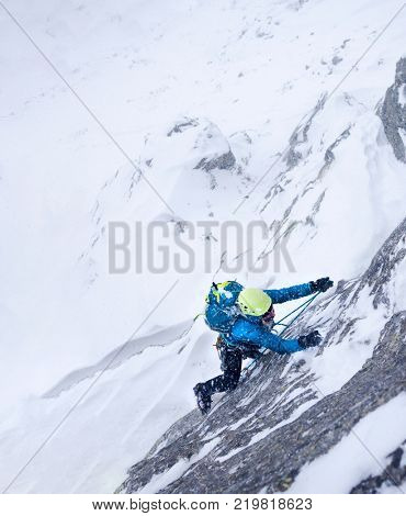 Female climber in the storm during an extreme winter climb. West italian Alps, Europe.