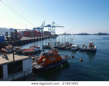 Cranes boats and containers at sea port