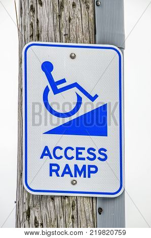 Blue and white sign letting people know there is a wheelchair access ramp nearby