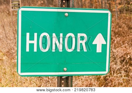 Green and white sign for the village of Honor