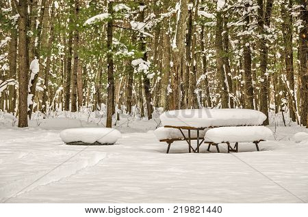 Picnic table and fire pit are buried under a fresh snowfall in a camping area in Michigan