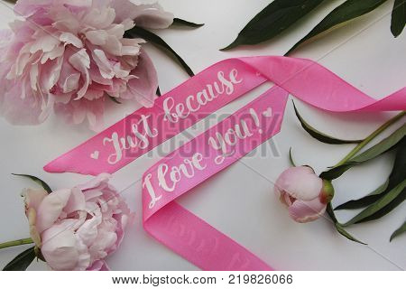 Flat lay composition with satin pink ribbon with modern calligraphy inscription `just because I love you` and peonies on white background for postcard, poster