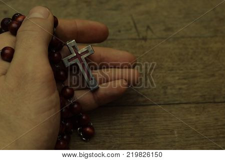 Wooden cross in the hand with focus on the cross. Beautiful background.Religion concept.