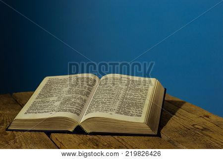 Bible on a old wooden table.  Beautiful blue background.Religion concept.