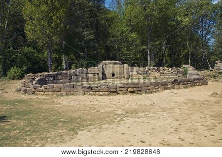 A large dolmen with stone surroundings. A dolmen is a type of single-chamber megalithic tomb, usually consisting of two or more vertical megaliths supporting a large flat horizontal capstone.