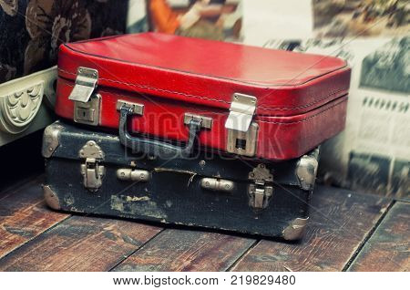 Red and blue old leather suitcase lying on the table.