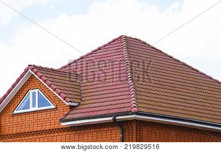 The house with a roof of classic tiles. Roof tiles made of baked clay on the roof.