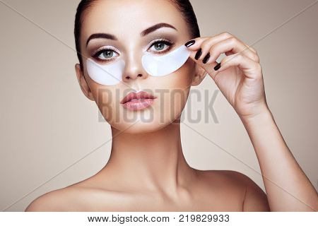 Portrait of Beauty Woman with eye Patches showing an effect of Perfect Skin. Beautiful Face of young Woman with clean Fresh Skin and bare shoulders on beige background. Brunette Spa Girl.
