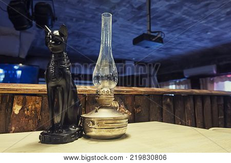 The figure of a black cat standing on the table next to a kerosene lamp.