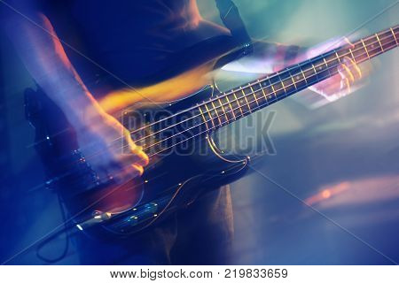 Colorful blurred rock music background bass guitar player on a stage with colorful illumination