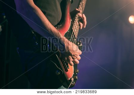 Closeup vintage toned photo of bass guitar player hands soft selective focus live music theme old style effect