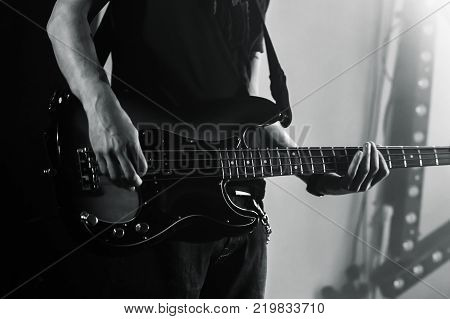 Hands of a bass guitar player live music theme black and white