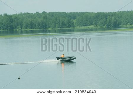 inflatable rubber boat with an outboard motor in the lake