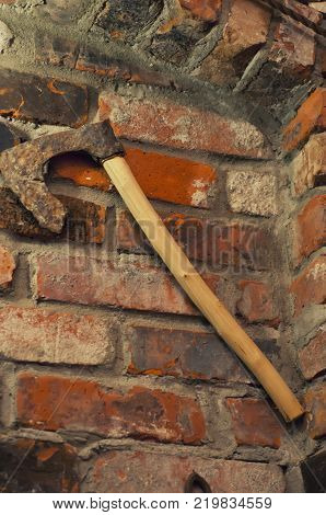 Stylish stone wall background and axe. The axe on the brick wall