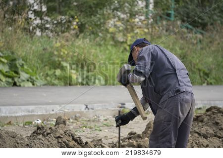 a worker with an iron chain and a sledgehammer to hammer the rod