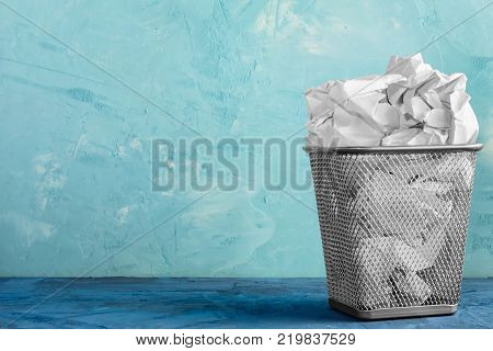 A trash can for paper. Beautiful blue background with place for text. A full trash can for crumpled paper sheets.