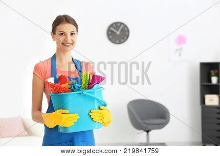Young woman with cleaning supplies in flat