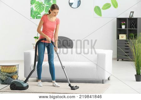 Young woman hoovering carpet at home