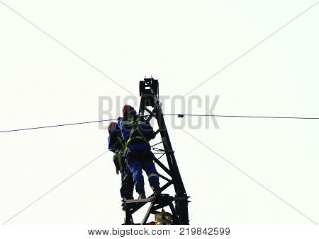 background in white  Silhouette electrician work installation of high voltage in high voltage stations safely and systematically over blurred poster