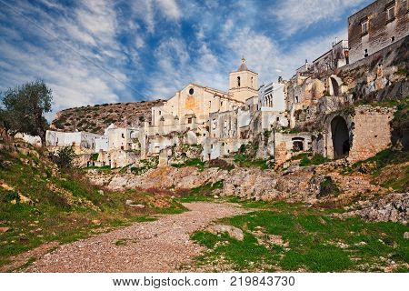Ginosa, Taranto, Puglia, Italy: landscape of the old village partly abandoned with the ancient church and the cave houses carved into the tufa rock