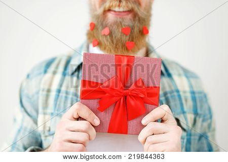 Cropped shot of romantic bearded male holds present box in front, going to make surprise for girlfriend, isolated on white background. Unrecognizable fashionable young guy with wrapped gift box.