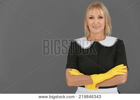 Mature charwoman on grey background