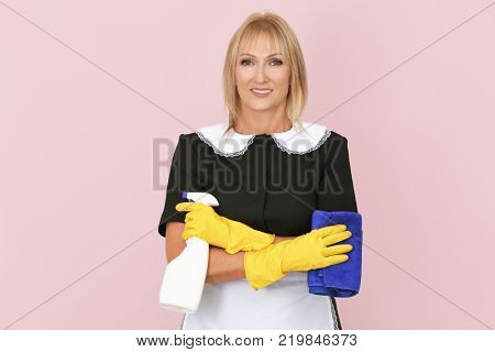 Mature charwoman with bottle of detergent and rag on color background