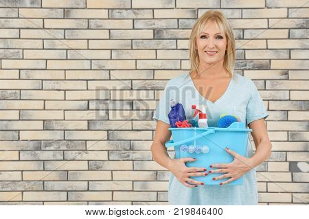 Mature woman with cleaning supplies against brick wall