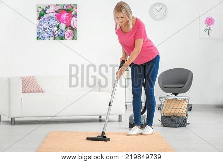 Mature woman hoovering carpet with vacuum cleaner at home