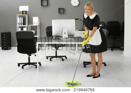 Mature charwoman mopping floor in office