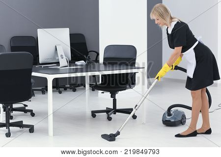 Mature charwoman hoovering floor in office with vacuum cleaner
