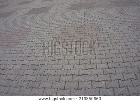 Texture of gray and yellow patterned paving tiles on the ground of street perspective view. Cement brick squared stone floor background. Concrete paving slab flagstone. Sidewalk pavement pattern.